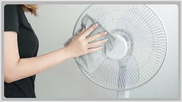 Wipe down the oscillating fan with the dry cloth